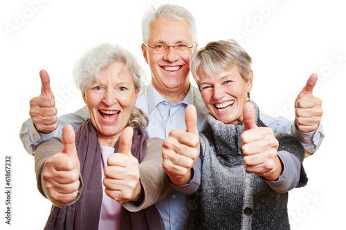 Photographie  Drei Senioren halten glücklich Daumen hoch