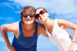 Closeup of happy young couple in sunglasses smiling on tropical