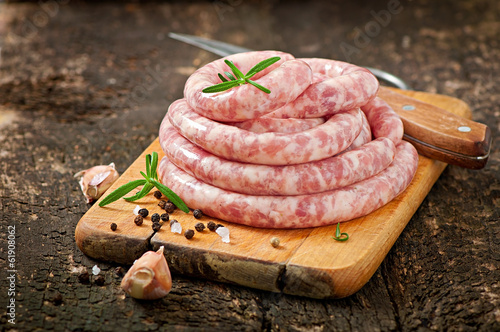 Fotografia Fresh raw sausage on the old wooden background