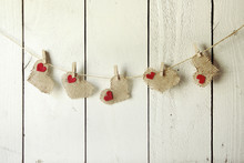 Happy Valentine Burlap Hearts Hanging On A Wood Wall