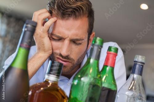 Obraz na plátně Drunk businessman slumped beside many spirit bottles