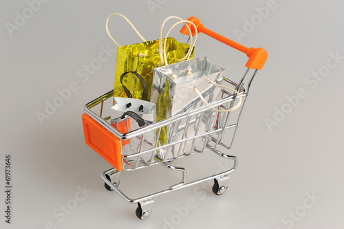 Poster Shopping cart with packages on gray
