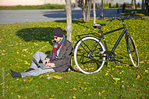 Poster Cycling Young man working on a laptop in an autumn park. His bicycle st