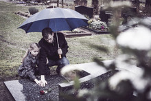 Father And Daughter Visiting Grave Of Deceased Mother