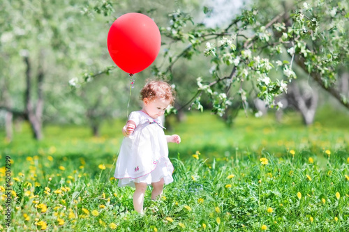 Sweet baby girl playing with a big red balloon Poster