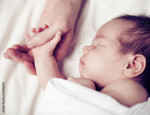 Fototapeta Newborn baby and his father's hand - care and safety concept obraz