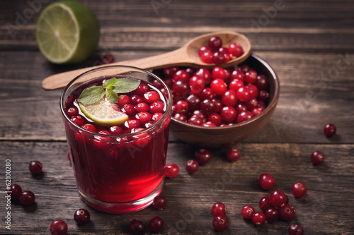 Fotografia  Cranberry juice on old wooden table