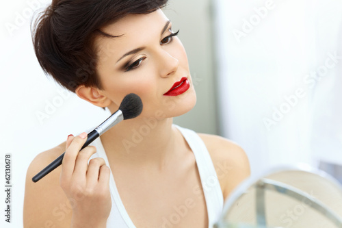 Fotografie, Obraz  Beauty Girl with Makeup Brush. Natural Make-up for Brunette