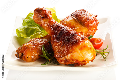 Fototapeta Grilled chicken legs and vegetables on white background obraz
