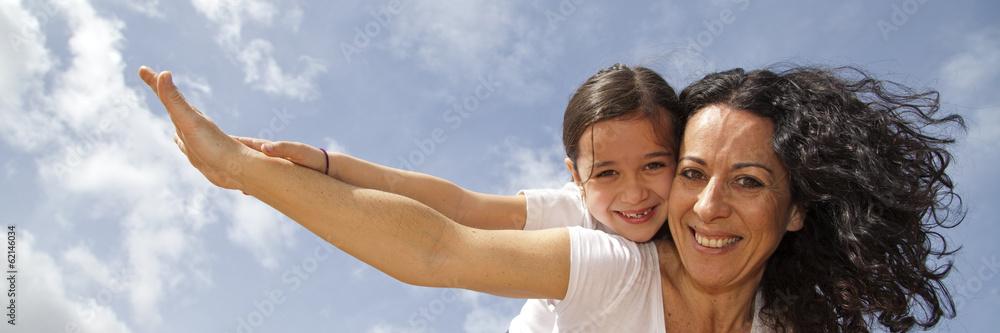 Fotografía  Madre e hija sonriendo y volando con el cielo de fondo