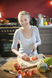 beautiful young woman slicing tomatoes on her kitchen's table