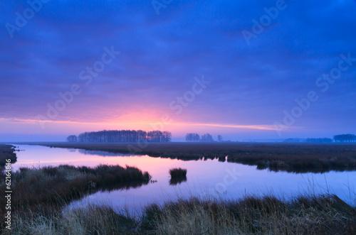 Purple, spring sunrise at a river.