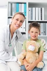 Friendly doctor with boy holding teddy bear