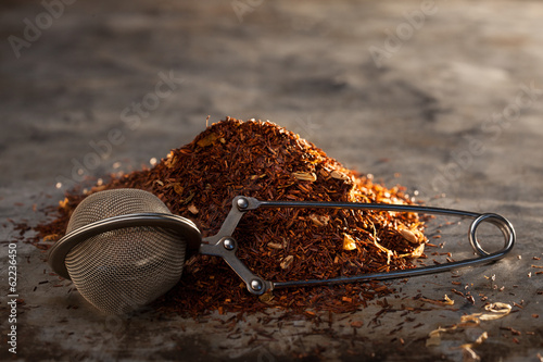 Fényképezés  Rooibos Tea and tea-strainer on a metal texture