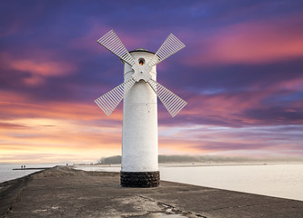 Fototapeta Morze Stawa Mlyny Lighthouse windmill with dramatic sunset sky, Swinoujscie, Poland.