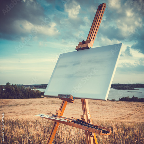 Fotomural canvas rests on a easel on lake landscape, retro stylized