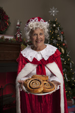 Mrs Claus Holding Fresh Baked Cinnamon Rolls By Christmas Tree