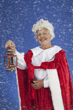 Mrs Claus Holding A Lantern In The Snow Searching For Santa