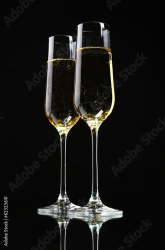 Glasses of champagne, on black background
