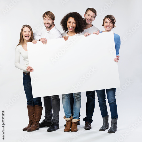 Fotografía  Lachende Junge Leute zeigen weißes Plakat