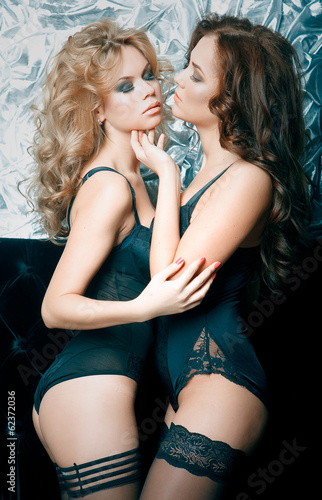 Two beautiful women in lingerie hugging on sofa