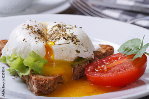 sandwich with salad, open poached egg on a white plate - 62376010