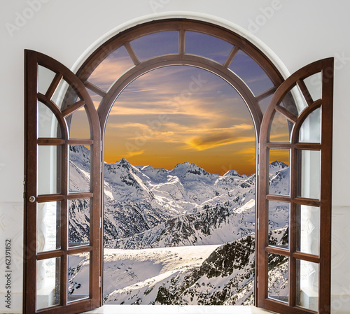 Obraz na płótnie Arch door opened with views of the peaks of snowy mountains and