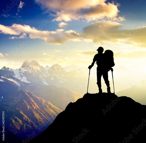 Sillhouette of a tourist on the high mountain. Canvas Print