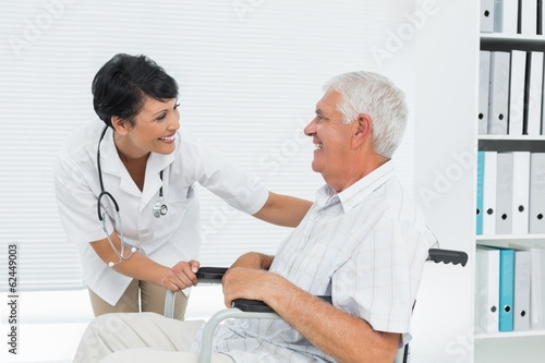 Fotografía  Female doctor talking to senior patient in wheelchair
