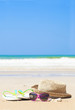 flip flops straw hat and sunglasses on tropical beach with waves
