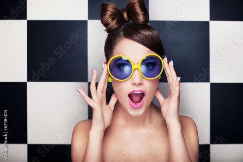 Fototapeta Attractive surprised young woman wearing sunglasses