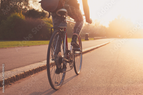Young woman cycling in the park at sunset