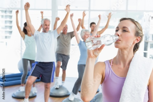 Fototapeten Tanzschule Woman drinking water with people stretching hands at fitness