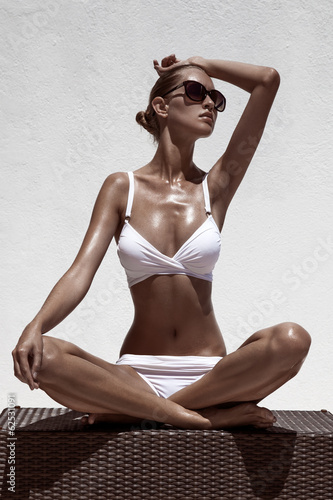 Beautiful tan female model posing in bikini and sunglasses. Agai