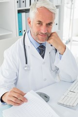 Mature male doctor at desk in the medical office