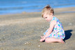 Girl plays with seashells sitting at s shore of the sea