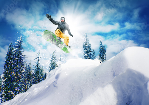 Fotografering Snowboarder jump against sky and trees
