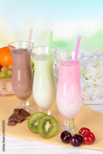 Naklejka - mata magnetyczna na lodówkę Milk shakes with fruits on table on light blue background
