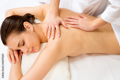 Fotografie, Obraz  Masseur doing massage on the back of woman in the spa salon.