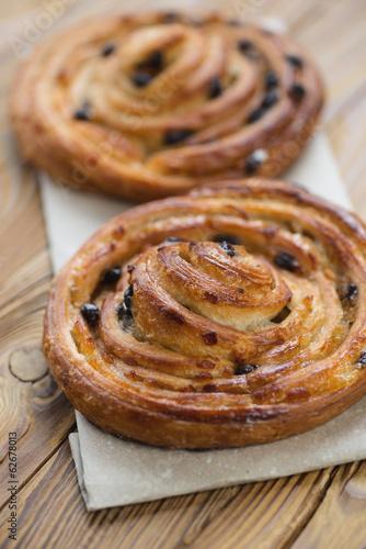 Foto op Plexiglas Bakkerij Sweet french roll buns over wooden background, vertical shot