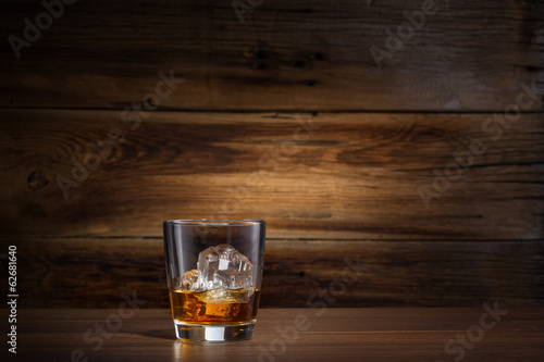 glass of whiskey with ice on a wooden background Canvas Print
