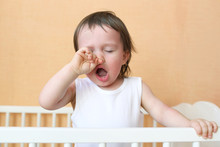 Yawning Baby In White Bed