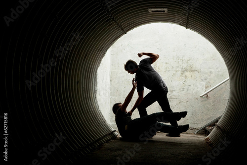 Canvas Print Young man being mugged in a dark tunnel