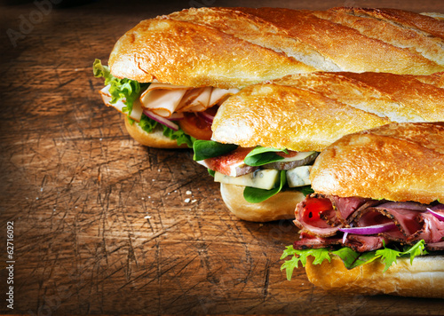 Staande foto Snack Three tasty baguettes with savory fillings