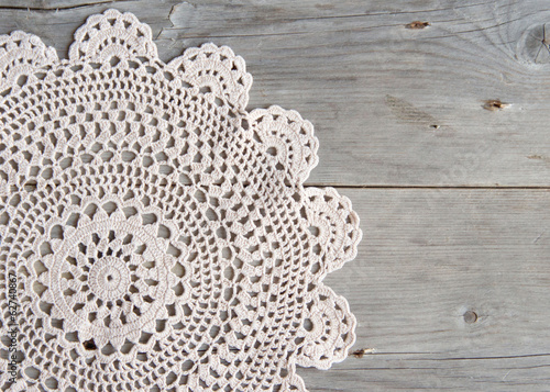 Valokuva  Crochet doily over old grey wood
