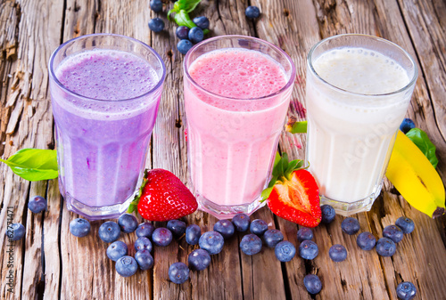 Tuinposter Milkshake Fresh milk, strawberry, blueberry and banana drinks on wodeen