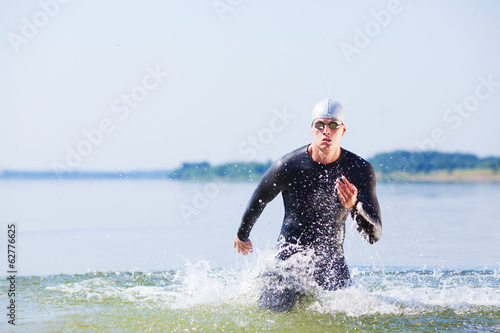Triathlete running out of the water Canvas Print