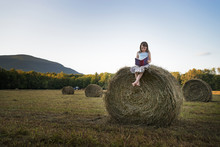 A Field Full Of Tall Rounded Hay Bales, And A Young Girl Sitting On The Top Of One Large Bale.