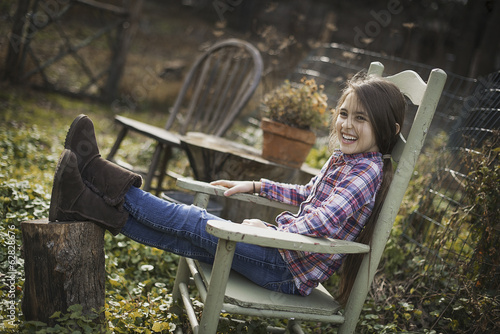 Fotobehang Tuin A young girl sitting in a wooden chair in a garden, with her feet up on a log.