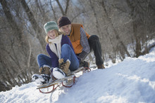 Winter Scenery With Snow On The Ground. A Man Pushing A Young Woman From The Top Of A Slope On A Toboggan.